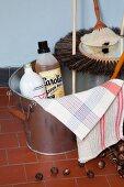 Zinkeimer mit Putzmittelflaschen, Tüchern und speziellen Besen; Waschnüsse auf dem Fliesenboden
