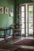 Rollbarer Servierwagen als Telefontischchen in Wohnraum mit grünen Wänden und geöffneter Tür zum Garten