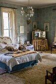 Nostalgisches Schlafzimmer in Blau mit Schminktischchen, Kronleuchter und Bett