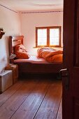 Traditional wooden bed below window in simple farmhouse bedroom
