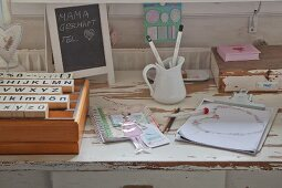 Set of old stamps, small chalkboard and vintage utensils on old table with drawer