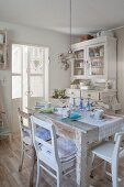 Shabby-chic table with pastel place settings, old kitchen chairs and antique white dresser in background