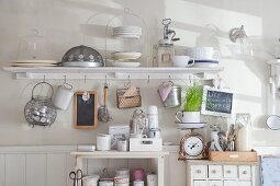 Shelf with cup hooks, small chest of drawers and open shelves of various nostalgic kitchen implements