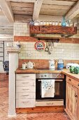 Rustic interior with white drawers in base units of open-plan kitchen