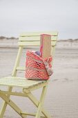 Straw mat in crocheted beach bag on wooden chair on beach