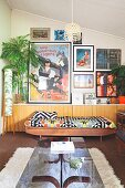 Glass-topped coffee table and couch with ethnic blanket against half-height, continuous sideboard below collection of pictures on wall