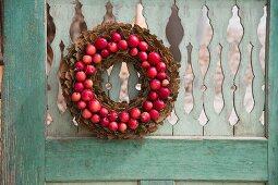 Kranz aus Baumrindenstücke und kleinen, roten Äpfeln an verwitterter Holztür aufgehängt