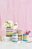 Tins covered with washi tape used as pen holders and vases against pink background