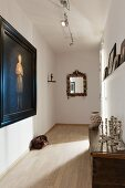 Narrow corridor with traditional ambiance; oil portrait in black frame and collection of silver candlesticks on antique cabinet
