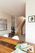 Wooden dining table in open-plan interior with African stool at foot of staircase
