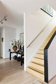 Staircase with wooden treads and objets d'art on glass table in niche in open-plan interior