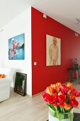 Red and orange tulips in front of male nude artwork on red-painted accent wall in modern interior