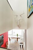 View down staircase with stylised hunting trophy on wall to open-plan, modern interior with dining set