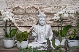 Potted herbs and white orchids next to Buddha statue in front of white love-heart hung on wooden wall