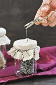 Old jam jars used as string dispensers; hand holding scissors