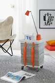 A table lamp and a cup of coffee on a mobile side table made from a stack of newspapers, wooden boards and straps