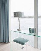 Plexi-Hocker mit Sitzkissen und puristischer Konsolen-Glastisch vor Fensterfront mit Seeblick