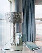Tischleuchte mit stilisiertem, silbernem Baumstammfuss auf Glastisch in elegantem Schlafzimmer mit Seeblick