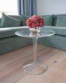 Überecksofa als Hintergrund für kleinen Tulpentisch aus Acrylglas mit Hortensienblüte