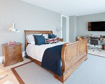 Spacious room with Union Flag scatter cushions on solid wooden bed and desk and swivel chair in background
