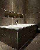 Braun gefliestes Badezimmer mit Badewanne und indirekt beleuchteter Ablagenische