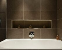 Braun gefliestes Badezimmer mit Ablagenische über der Badewanne