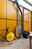 Bicycle and locker on castors next to black Bullerjan stove in front of tall wood and metal wall