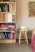 Table lamp on retro wooden stool next to bookcase made from reclaimed boards