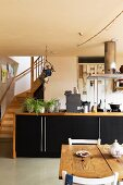 Dining area in front of kitchen counter with wooden frames and black doors; foot of staircase to one side