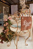 Vintage chair made from rusty, curved metal decorated for wedding