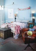 Vintage-style, metal four-poster bed and antique leather armchair in bedroom