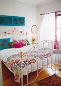 White metal bed in bright bedroom with various accents of bright colour