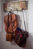 Various bags hanging on vintage wooden coat rack with pattern of roses