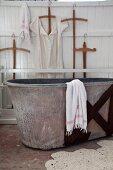 Old zinc bathtub and crocheted bathmat in vintage-style bathroom