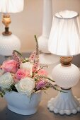 White porcelain table lamp next to romantic posy of roses