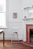 Antique metal chair next to fireplace with red tiled surround