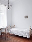 Metal bed and table in simply furnished spare bedroom