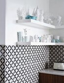 Black and white, geometric wall tiles below shelves of white crockery and ornaments