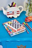 Colourful exercise books and felt-tip pens in front of retro teapot used as pen holder on blue table
