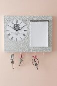 Hand-crafted key hanger with clock and notepad mounted on pink wall
