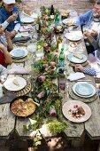 Rustikal gedeckte Tafel mit knuspriger Ente und Kartoffel-Mozzarella-Gratin