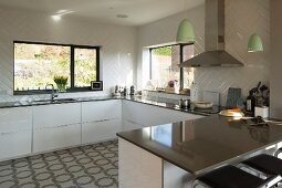 U-shaped, white, designer fitted kitchen with glossy worksurface below windows; breakfast bar and bar stools in foreground
