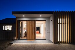 Twilight sky over modern house with illuminated entrance and view of interior