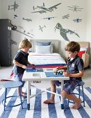 Two children playing on table in child's bedroom on blue and white striped rug; aeroplane wall sticker in background