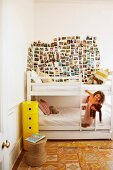 Little girl climbing on ladder of white bunk beds below large collection of postcards on wall