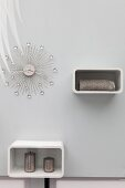 Elegant wall clock with crystal decorations and two white shelving units on pale wall