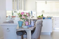 Elegant upholstered chairs, lilies and crockery on table in elegant dining area of open-plan kitchen