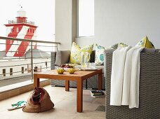 Floral scatter cushions on wicker sofa and coffee table on balcony with view of red and white lighthouse