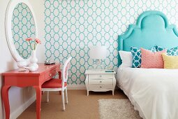 Bed with turquoise headboard and salmon-pink dressing table in bedroom
