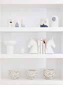 Decorative white vessels and china horses heads on white shelves
